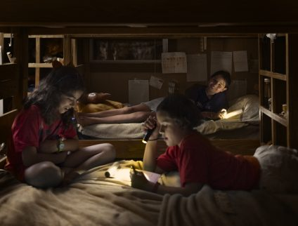 Campers reading with flashlights