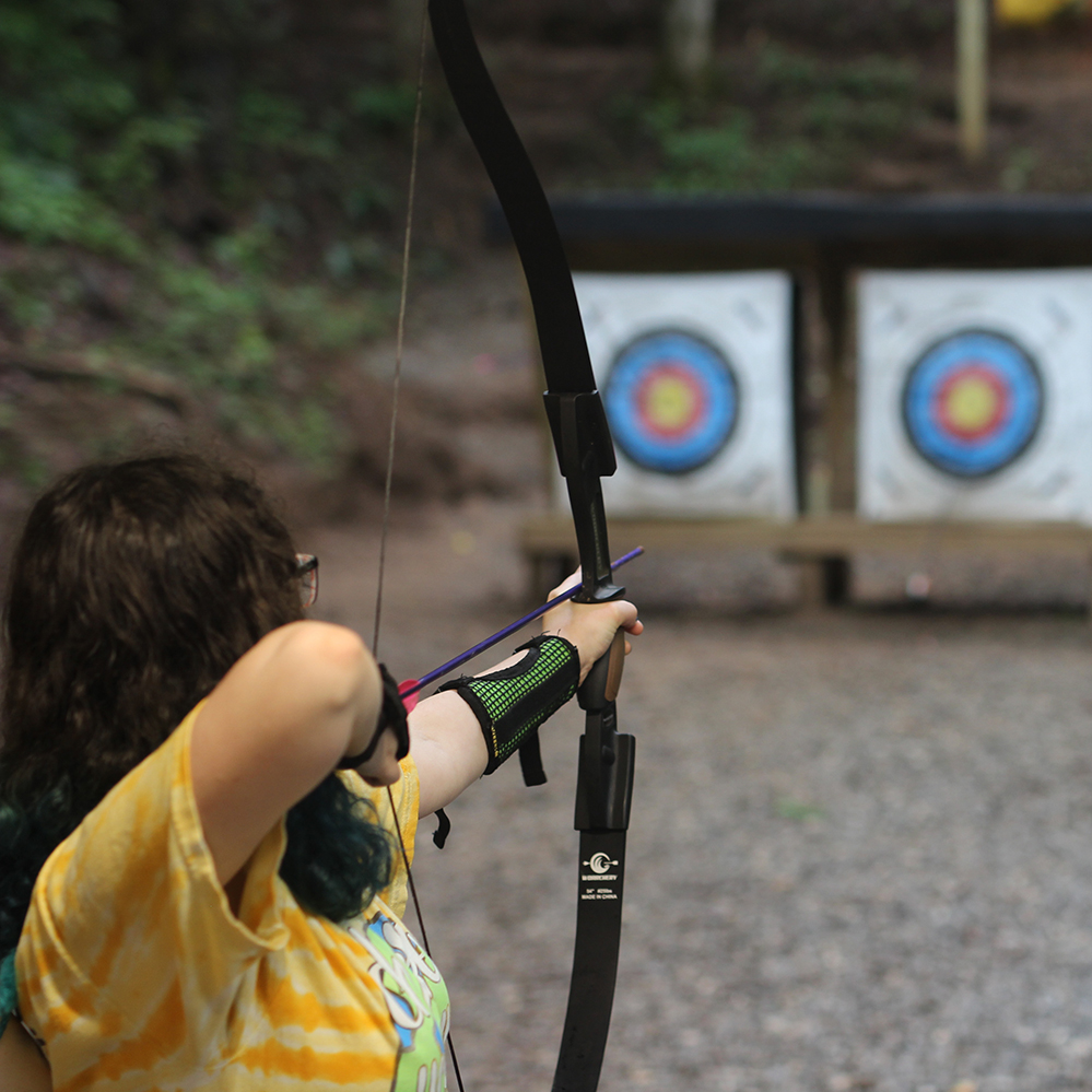 Picture of a girl from behind pulling back on an archery bow and shooting for the target at Ramah Darom's archery course