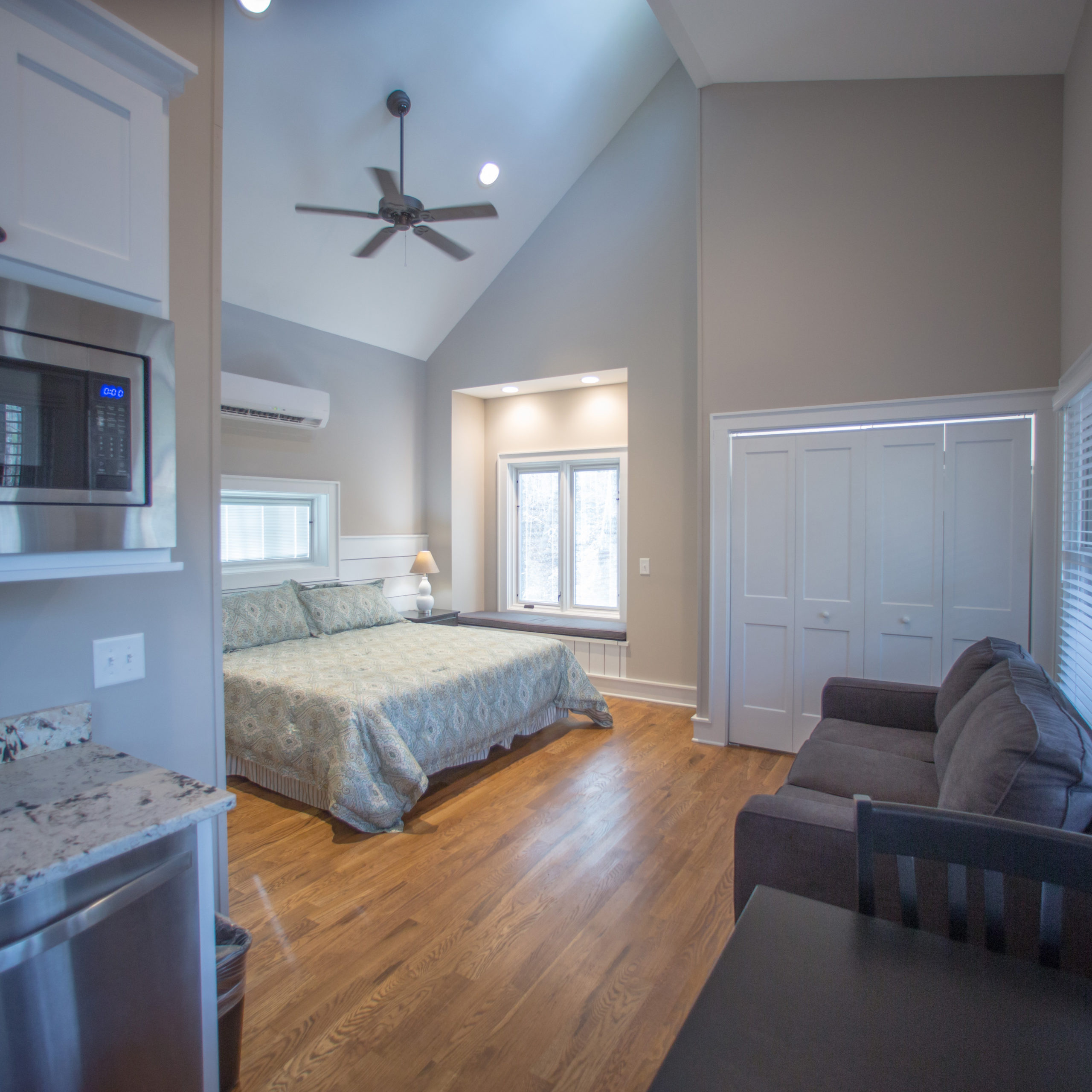Picture of the inside of a luxurious studio cottage at Ramah Darom showing the king-size bed, pull out sofa, table and a corner of the kitchenette