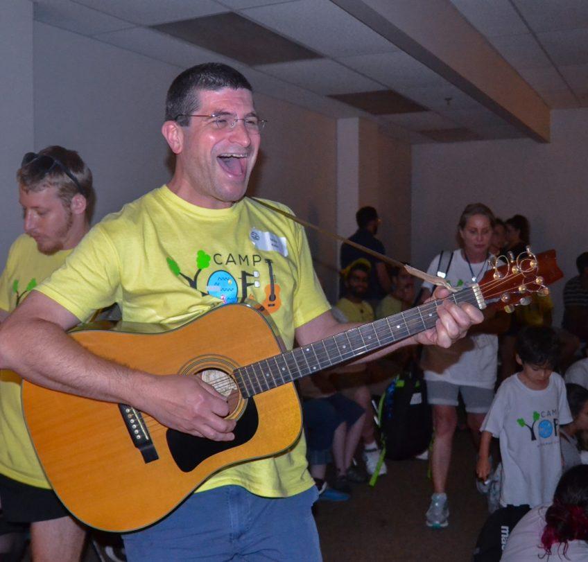 Matt Kalin singing at Camp Yofi with a yellow shirt, a wide smiling mouth and a guitar