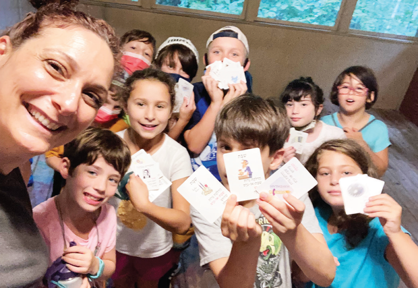 Snait zBen-Herut and campers playing a game with Hebrew cards